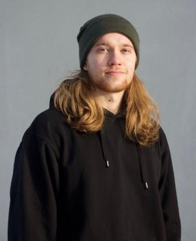 Hieman hymyilevä nuori henkilö katsoo kameraan edestä kuvattuna. Punertava lyhyt parta, pitkät vaaleat hiukset, musta huppari.