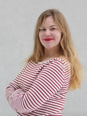 Nuori henkilö poseeraa hymyillen kameralle sivuprofiilissa. Pitkät vaaleat hiukset ja valko-punaraidallinen paita.