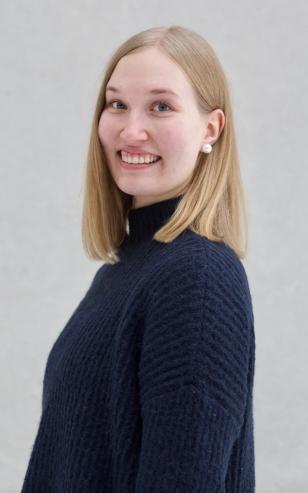 Nuori henkilö hymyilee kameralle sivusta kuvattuna. Olkapituiset vaaleat hiukset, siniset silmät ja tummansininen villapaita.