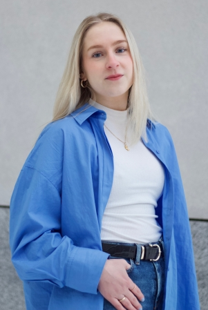 Nuori henkilö katsoo kameraan. Vaaleat keskipitkät hiukset, siniset silmät ja sininen paita.